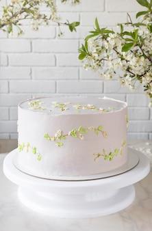 Hochzeit rosa kuchenkuchen auf einem ständer zwischen kirschblütenzweigen. zartes dekor auf der torte.