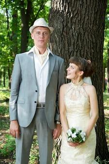 Hochzeit schöne junge braut und bräutigam, die in einem park stehen