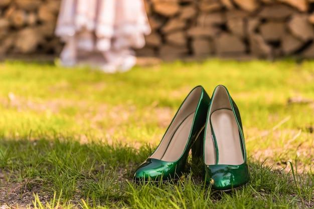 Hochzeit smaragdgrüne brautjungfernschuhe auf dem grünen gras auf dem hintergrund des kleides