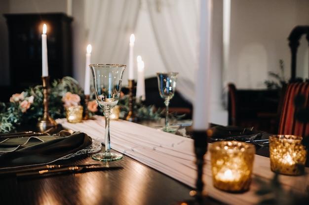 Hochzeit tischdekoration mit blumen auf dem tisch im schloss, tischdekoration zum abendessen bei kerzenschein. abendessen mit kerzen.
