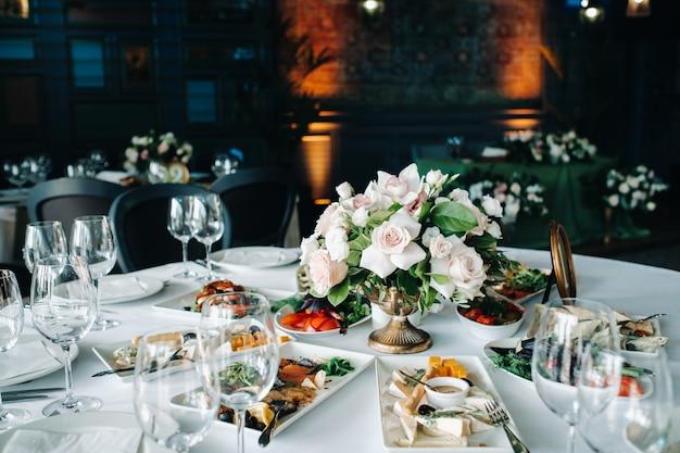 Hochzeit tischdekoration mit blumen auf dem tisch im schloss, tischdekoration zum abendessen bei kerzenschein