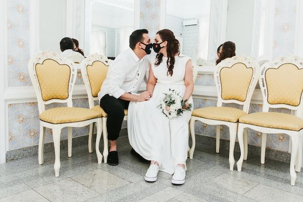Hochzeit während der coronavirus-epidemie. braut und bräutigam in medizinischen schutzmasken. verheiratete und covid-19-pandemie.