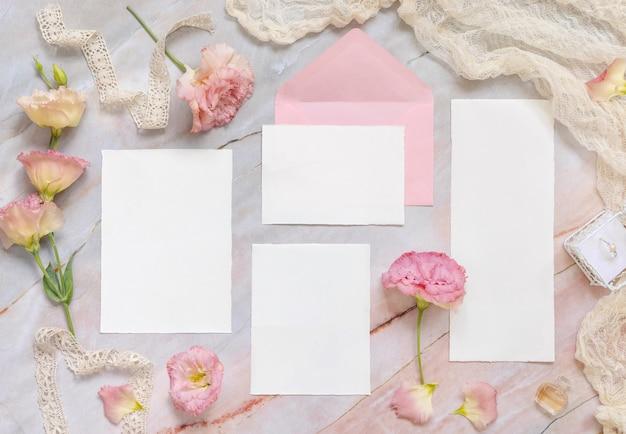 Hochzeits-briefpapier-set mit umschlag auf einem mit blumen und bändern dekorierten marmortisch