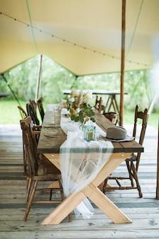 Hochzeits- oder abendessenempfangstisch im rustikalen stil eingerichtet