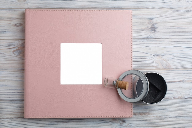 Hochzeits- oder familienfotoalbum auf holz. fotobuch und flash-laufwerk mit einer box in der nähe. rosa fotoalbum in einem lederbezug und mit schild. leder fotobuch mit kopierraum für text