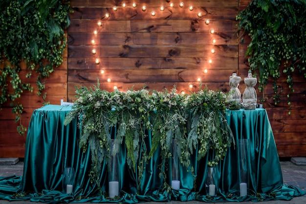 Hochzeitsbankett auf dem hintergrund des herzens der lampen im wald zwischen den bäumen auf der grünen spur
