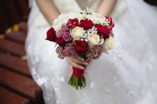 Hochzeitsblumen, hochzeitsblumenstrauß, die braut, die einen blumenstrauß des rotes und des pfirsiches, der molkereirosen und der weißen blumen, hochzeitszeremonie hält