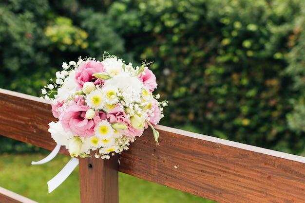 Hochzeitsblumenblumenstrauß gebunden auf hölzernem geländer im park