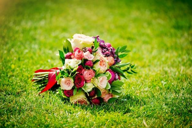 Hochzeitsblumenstrauß an einem sonnigen tag auf einem grünen rasen