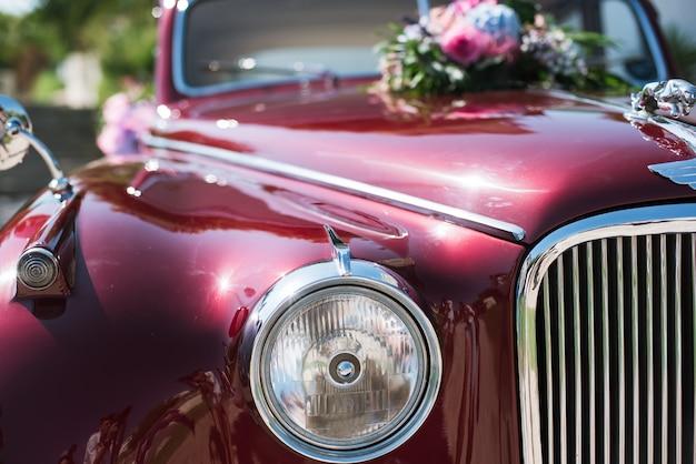 Hochzeitsblumenstrauß auf rotem weinlesehochzeitsauto.