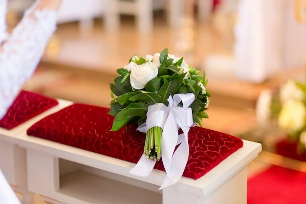 Hochzeitsblumenstrauß, der auf bank in der kirche während der hochzeitszeremonie legt