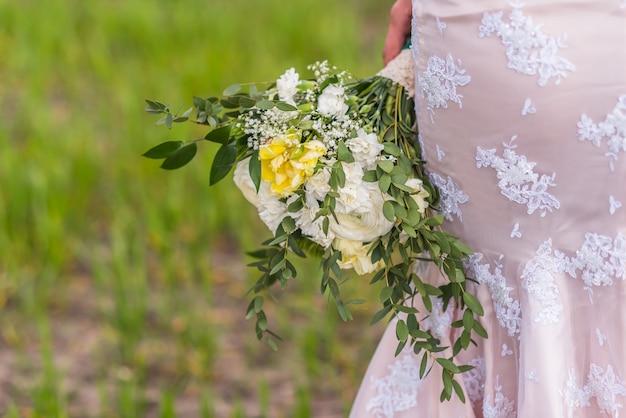 Hochzeitsblumenstrauß in den händen der braut auf dem hintergrund des kleides