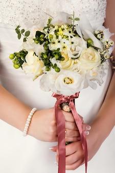Hochzeitsblumenstrauß in den händen der braut mit einem braunen band