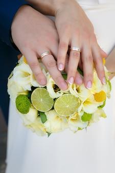 Hochzeitsblumenstrauß in den händen der braut und des bräutigams