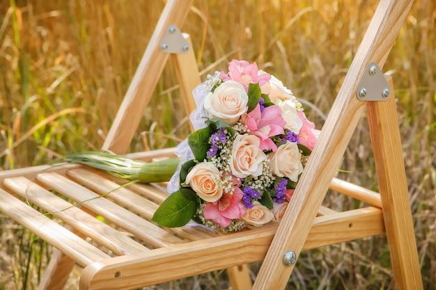 Hochzeitsblumenstrauß liegt auf den holzstühlen für hochzeitszeremonie.