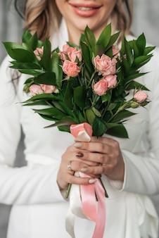Hochzeitsblumenstrauß mit rosa rosen in den händen der braut