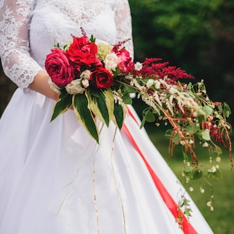 Hochzeitsblumenstrauß mit roten pfingstrosen und grünblättern in den händen der braut
