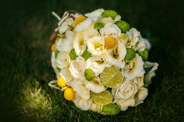Hochzeitsblumenstrauß von den beige rosen, vom zimt, von einer zitrone, von einem kalk auf einem grünen gras