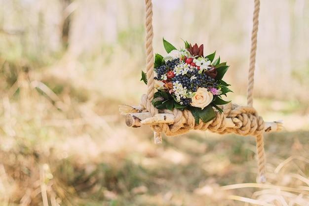 Hochzeitsblumenstrauß von dunklen beeren, rosen draußen auf dem verzierten schwingen