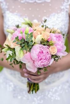 Hochzeitsblumenstrauß von rosen und von pfingstrosen in den händen der braut