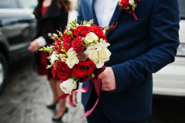 Hochzeitsblumenstrauß von weißen und roten rosen an hand des bräutigams.