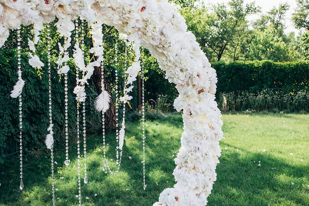 Hochzeitsbogen aus weißen blumen in runder form mit perlen und federn auf dem hintergrund der natur