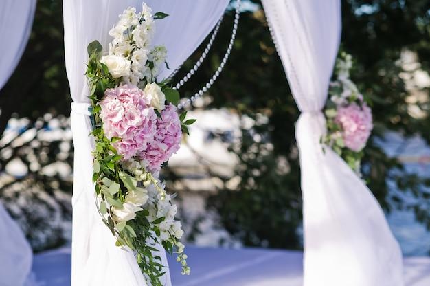 Hochzeitsbogen der braut und des bräutigams verziert mit blumen von rosen.