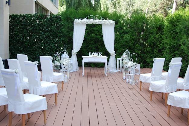 Hochzeitsbogen für zeremonie mit stühlen