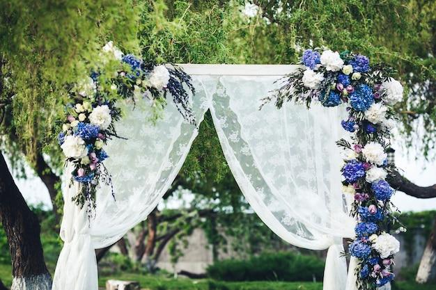Hochzeitsbogen mit stoff und blumen verziert.