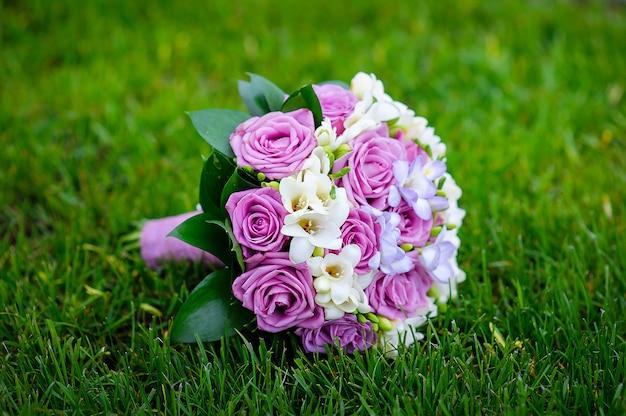 Hochzeitsbrautstrauß, der auf dem gras liegt
