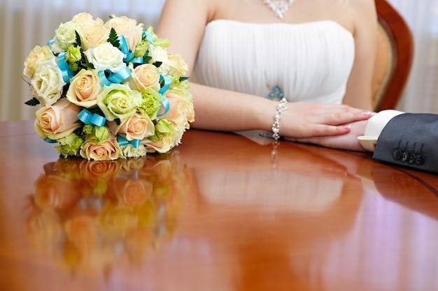 Hochzeitsbrautstrauß ist neben den frisch verheirateten händen.