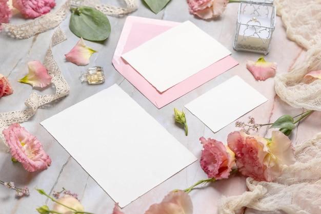 Hochzeitsbriefpapier-set mit umschlag auf einem marmortisch, der mit blumen und bändern dekoriert ist, nahaufnahme