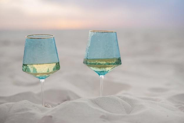 Hochzeitsbrille aus blauem glas im sand des strandes vergraben