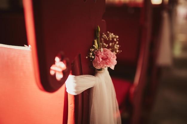 Hochzeitsdekor für stühle mit blumen in der kirche. hochzeitsblume und dekoration.