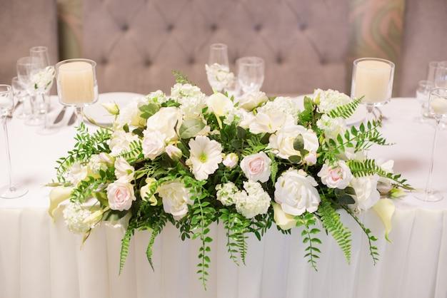 Hochzeitsdekor im innenraum, weiße blumen auf dem tisch, die tabelle mit kristallgläsern dienend.