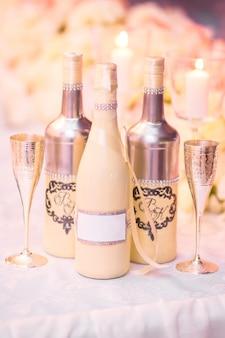 Hochzeitsdekor mit hochzeitsgläsern, flaschen, pfirsichen. dekoration eines hochzeitsfotoshootings. details einer hochzeitsdekoration.