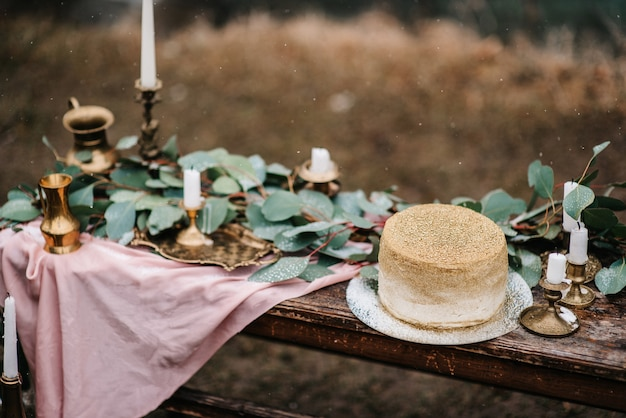 Hochzeitsdekoration mit einem goldenen kuchen auf einer holzbank vor einem wasserfallhintergrund