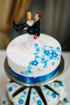 Hochzeitsdekoration mit kuchen auf einer holzbank vor einem wasserfallhintergrund