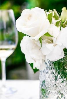 Hochzeitsdekoration tischdekor und floraler schönheitsstrauß aus weißen rosen im luxusrestaurant schön...