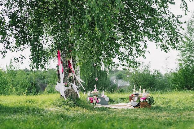 Hochzeitsdekoration von den blumen und dekorationen mit einer schaukel unter den bäumen im freien im sommer