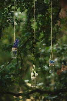 Hochzeitsdekorationen aus kleinen flaschen, die mit rosen und anderen blumen gefüllt waren, hingen im wald an einem faden zwischen bäumen
