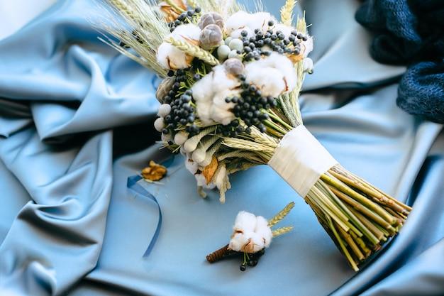 Hochzeitsdekorationen, blumen auf einem blauen stoffhintergrund. high angle view.