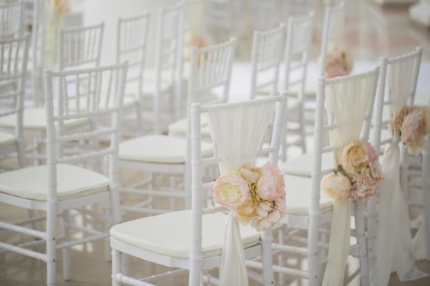 Hochzeitsdekorationen blumen auf stühlen. registrierung des hochzeitsausgangs, weiße stühle für die hochzeit dekoriert. hochzeits-setup-detail.