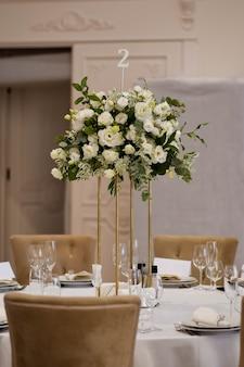 Hochzeitsdekorationen mit metallvase und weißen frischen blumenarrangements.
