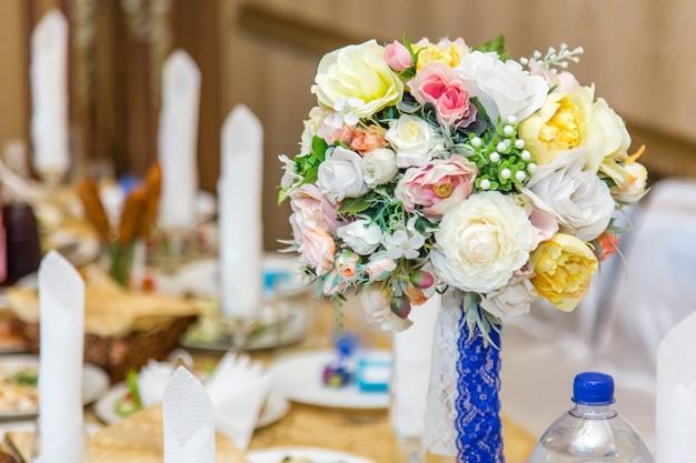 Hochzeitsdekorationssträuße von rosen auf einem tisch im restaurantinnenraum.