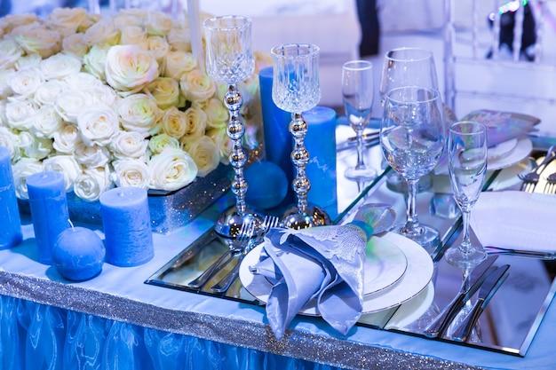 Hochzeitsdekoriertes restaurant mit blumensträußen und blauen kerzen