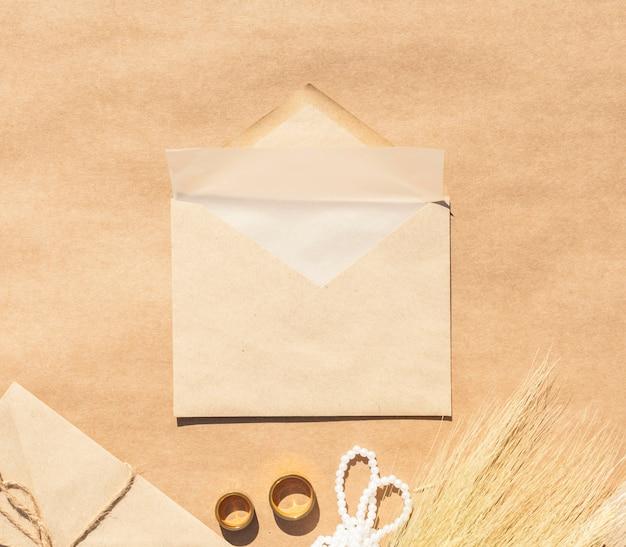 Hochzeitseinladung im umschlag mit papierhintergrund