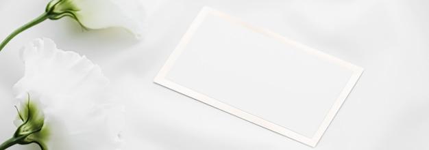 Hochzeitseinladung oder geschenkkarte und weiße rosenblüten auf seidenstoff als braut-flatlay-hintergrund b ...