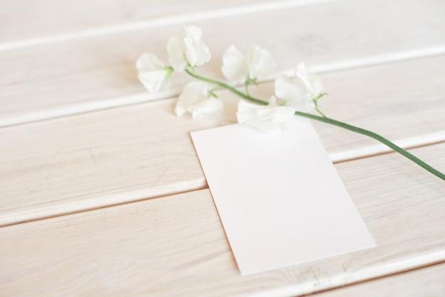 Hochzeitseinladungsgeburtstagsgeschenkgutschein für eine spa- oder pflege verzierte briefkarte auf einem weißen holztisch mit einem zweig der weißen blumen.