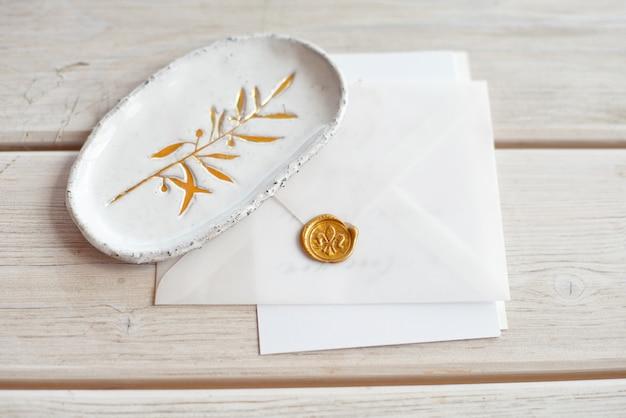 Hochzeitseinladungsgeburtstagsgeschenkgutschein für eine spa- oder pflege verzierte briefkarte auf einem weißen holztisch mit einer keramikplatte im rustikalen stil.